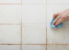 cleaning dirty shower and  bathroom tiles with mould with blue cloth